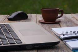 Laptop, notebook with pen and cup of coffee on a wooden table. Workplace outdoors