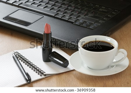 Laptop, notepad, pen, lipstick and cup of coffee on wooden desk.