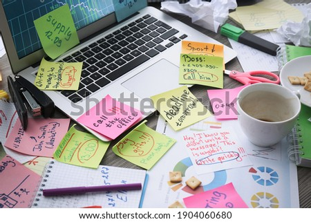 Laptop, notes and office stationery in mess on desk. Overwhelmed with work Stock fotó ©