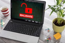 Laptop on a desk with malware concept on the screen