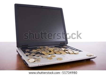 Laptop on a desk with many euro coins