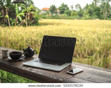 laptop on a wooden table in nature with a view to a green ricefield