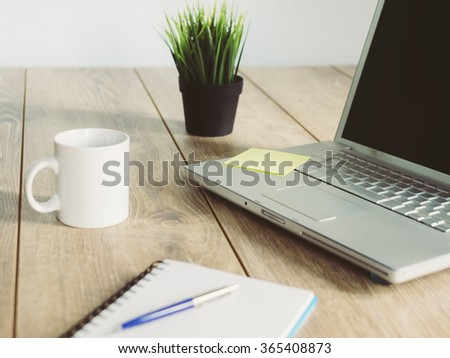 laptop on desk with a cup of...