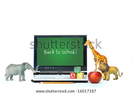 Laptop on desk with toy animals and apple on white