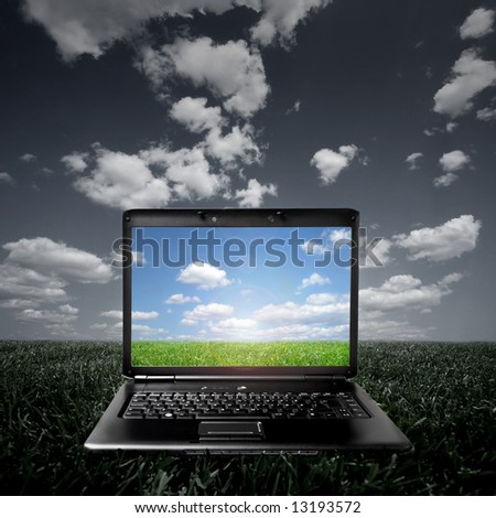 Laptop on green grass on a sunny day