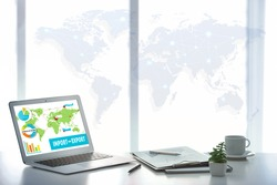 Laptop on table at office. World map and text IMPORT-EXPORT on screen. Wholesale and logistics concept