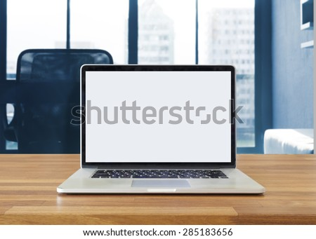 Laptop on table, on office background,blank screen