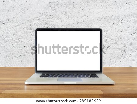 Laptop on table, on  white cement wall background,blank screen