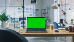 Laptop on the Desk in the Office Shows Green Mock-up Screen. In the Background Creative Modern Open Space Loft Office HUB with Professional Working