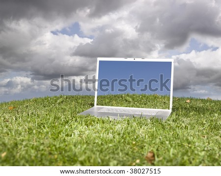 Laptop outdoors on a green field with a moody sky background