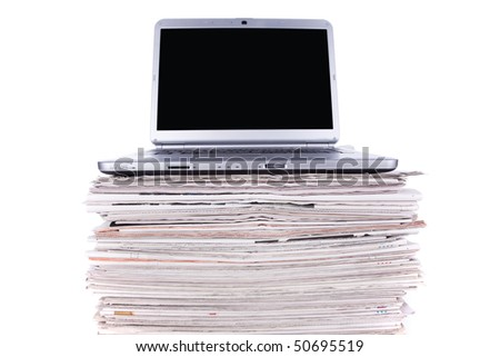 Laptop over a stack of newspapers for internet information access (isolated on white) - stock photo