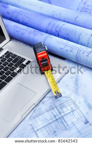 Laptop over blueprint of a residential structure design with other working tool