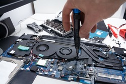 Laptop repair in a workshop, male hand holds a screwdriver