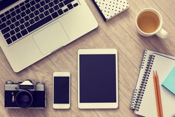 Laptop, smartphone, tablet, vintage camera and cup of tea on wooden table