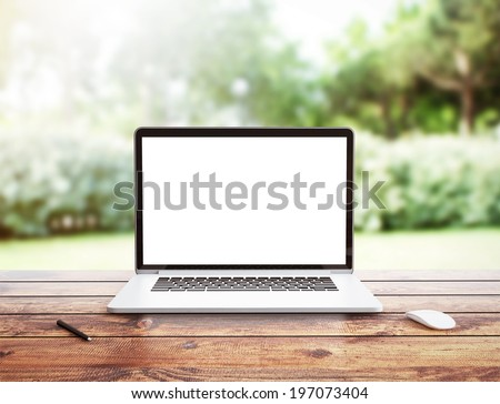 Laptop stands on a wooden table outdoors