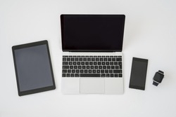 Laptop , tablet , smart phone and smartwatch.on table. Modern digital devices and gadgets.