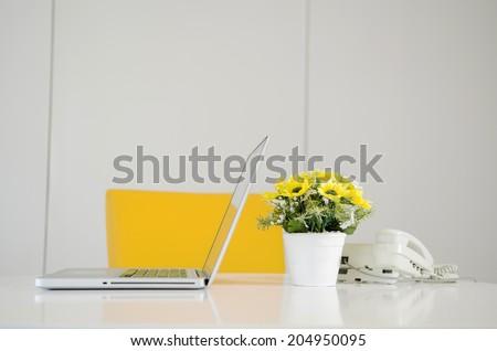 laptop telephone and flower in vase on desk