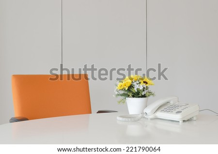 laptop telephone and flower in vase on desk, work space