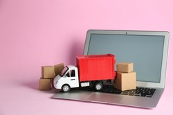Laptop, truck model and carton boxes on pink background. Courier service