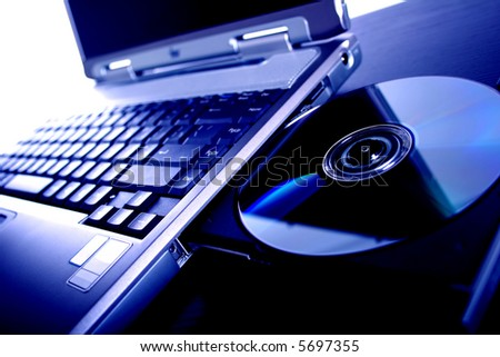 laptop with a disk dvd. blue tone