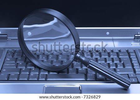 Laptop with a magnifying glass, concept of online security and investigation.