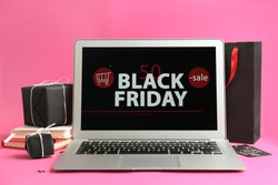 Laptop with Black Friday announcement, notebooks and gifts on pink background