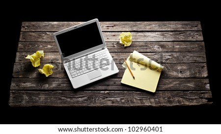 Laptop with blank notepad and pencil with sheets of crumpled paper on old wooden table. Workplace writer.