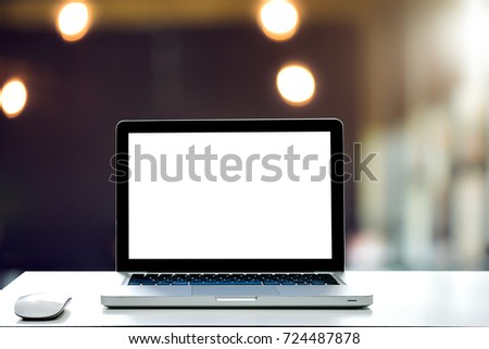 Laptop with blank screen and wireless mouse on desk white in cafe interior blurred background at light bokeh. #724487878