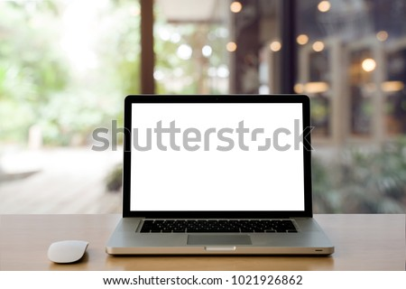 Laptop with blank screen and wireless mouse on Empty space Wooden Desk at home interior blurred background at light bokeh. #1021926862