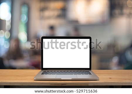 Laptop with blank screen on table. coffee shop blurred background.
