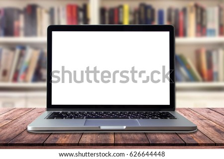 Laptop with blank screen on table in interior library
