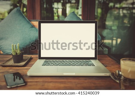 Laptop with blank screen on table. laptop computer on wood table. gray color laptop. laptop white screen. laptop and smartphone on table. laptop and coffee cup in cafe. laptop vintage tone.