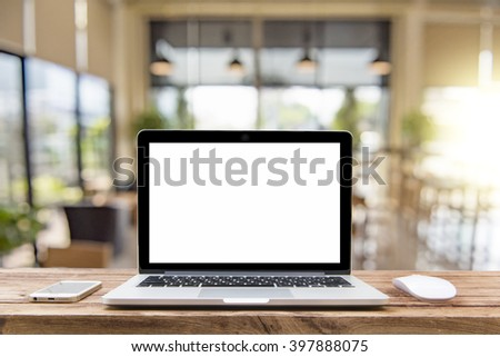 Laptop with blank screen on table of a cafe