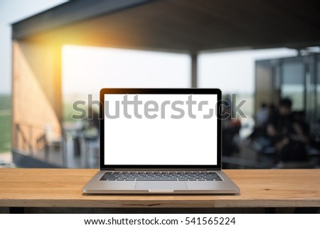 Laptop with blank screen on table of a cafe.