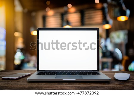 Laptop with blank screen on table of a cafe on Halloween.