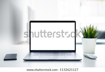 Laptop with blank screen on white table with mouse and smartphone. Home interior or office background #1132621127