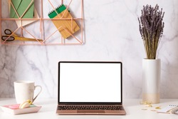 Laptop with blank white screen on home office desk interior. Stylish workplace mockup table view.