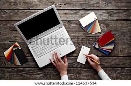 Laptop with color swatches with woman's hands holding pencil on old wooden table. Workplace designer.
