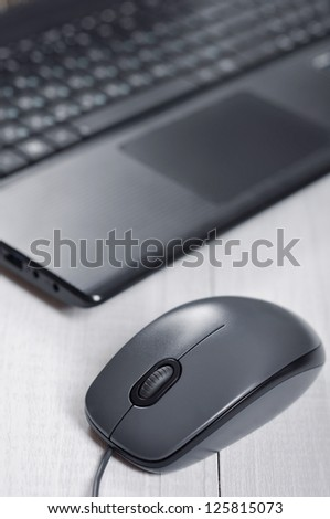 Laptop with computer mouse on the table closeup
