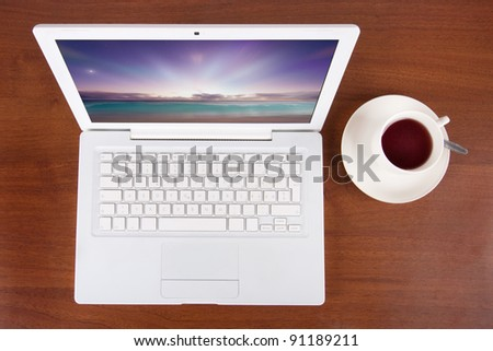Laptop with cup of tea or coffee - stock photo