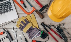 Laptop with DIY and construction tools isolated on wooden background