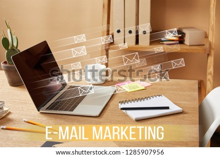 """laptop with email icons and """"email marketing"""" lettering on wooden table at home #1285907956"""