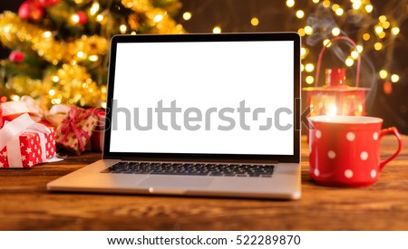 Laptop with empty screen on wooden table, blur Christmas tree and gifts on background