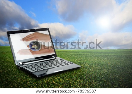 Laptop with globe protection symbol on display against green nature background