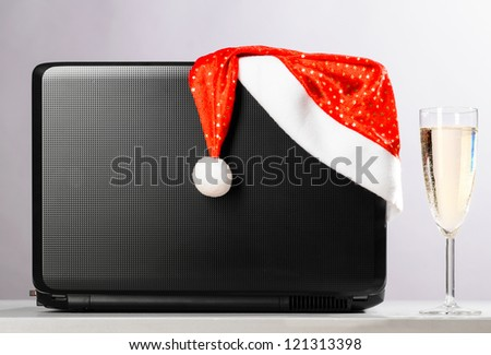 laptop with santa hat and sparkling wine on gray