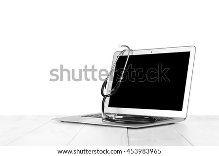 Laptop with stethoscope, isolated on white