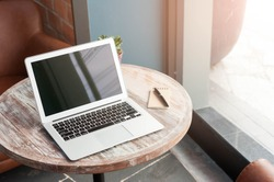 Laptop with tablet and pen on wooden table in coffee shop