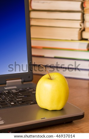 laptop with yellow apple on books background