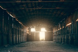 Large abandoned empty and dirty rusty iron hangar, creepy warehouse inside, toned