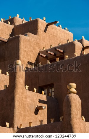 Large adobe building with luminaria on walls for the holidays